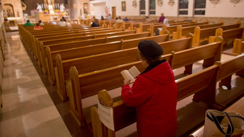 WOMAN PRAYS IN PEW AT WISCONSIN SHRINE